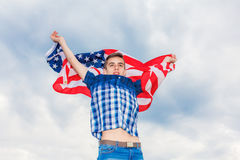 USA flag is held by a running guy in the background of a summer sky Royalty Free Stock Photography
