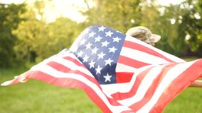 USA flag is held by a running guy in camouflage on the background of a summer park and sky Outdoor Patriotic day.  stock video