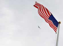 USA Flag with helicopter and sky background. The USA Flag with a helicopter and sky background. The flag is on a flag pole and waving in the wind, with its red Royalty Free Stock Photos