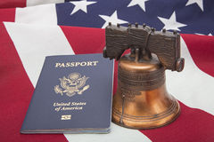 USA flag liberty bell passport success concept. The liberty bell and American freedom flag rests with the United States of America passport book.  The right to Stock Photo