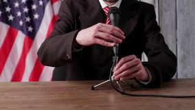 USA flag, man and microphone. Businessman speaking into the microphone. Time for motivational speech. Very important message stock footage