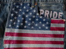 USA flag with pride word on denim blue jeans background concept. USA flags with pride word on denim blue jeans background concept royalty free stock photo