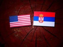 USA flag with Serbian flag on a tree stump isolated. USA flag with Serbian flag on a tree stump royalty free stock photo