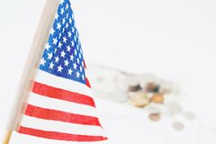 USA flag, stack of coins and dollars in background, selective focus. Travel America Royalty Free Stock Photo