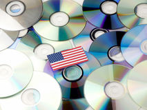 USA flag on top of CD and DVD pile isolated on white. USA flag on top of CD and DVD pile isolated Royalty Free Stock Images