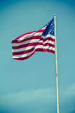 USA Flag Vertical. A vintage style photo of the american flag waving on a pole with a vignette against a blue sky Royalty Free Stock Image