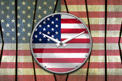 USA flag wall clock reads ten past ten o'clock on USA flag paint. Ed on old plank wood background, concept of freedom Stock Photo