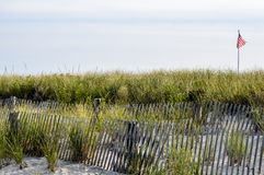 USA flag waving of the beaches of New England. The beach with sand, fences and marsh grasses growing. Plenty of space to write your message in the sky Royalty Free Stock Images