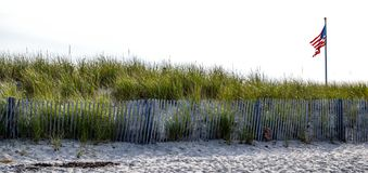 USA flag waving on a New England beach. USA flag waving off the beaches of New England. The beach with sand, fences and marsh grasses growing. On a bright sunny Royalty Free Stock Photos