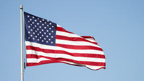 USA flag waving in the wind against a clear blue sky. American flag waving in the wind against a clear blue sky stock footage