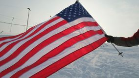 USA flag waving in the wind, highly detailed fabric texture. US flag on ski slope winter day stock footage