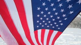USA flag waving in the wind - highly detailed fabric texture. US flag on ski slope winter day stock footage