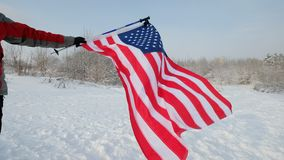 USA flag waving in the wind - highly detailed fabric texture. US flag on ski slope winter day stock video