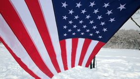 USA flag waving in the wind, highly detailed fabric texture. US flag on ski slope winter day stock video footage