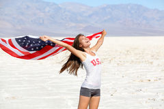USA flag - woman athlete showing american flag. US sport athlete winner cheering waving stars and stripes outdoors in desert nature. Beautiful cheering happy Royalty Free Stock Photos