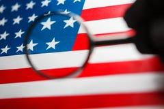 USA-flagga som ser till och med ett förstoringsglas Studie av historien och kulturen av landet av Förenta staterna Begreppet av royaltyfri fotografi