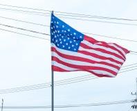USA flagga som vinkar med en molnig himmel Arkivfoton