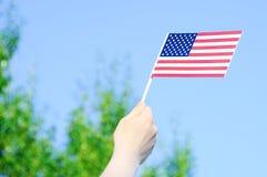 USA-flaggan i händer mot en blå klar himmel och gröna träd royaltyfri foto