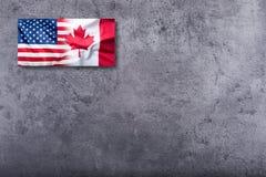 USA flaggan och Kanada sjunker på konkret bakgrund Arkivbild