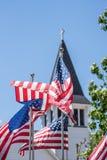 USA-flaggor på blåsig dag med vit kyrktar kyrktorn i bakgrund royaltyfri fotografi