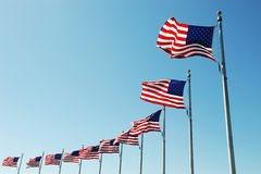 USA flags in a row against blue sky. Waving USA flags in a row against blue sky Royalty Free Stock Photo