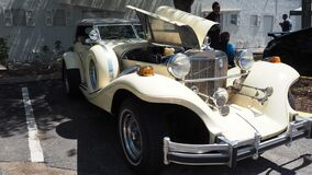 Cream color 1982 Excalibur phaeton convertible with engine doors open
