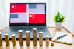 USA gegen China-Flagge auf Laptopschirm auf Holztisch Gold- und Silberm?nzen sind- Front des Laptops und Notizbuch mit Stift stockbilder