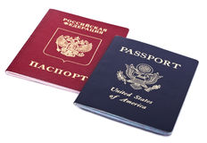 Double Nationality - American & Russian. USA and German passports isolated on white background. Both of the passports are decorated with their countries' coats Royalty Free Stock Photos