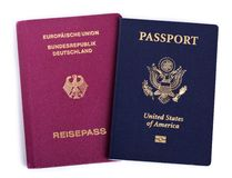 Double Nationality - American & German. USA and German passports isolated on white background. Both of the passports are decorated with very similar coats of Stock Photography