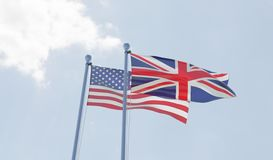 USA and Great Britain flags waving against blue sky. Stock Photo