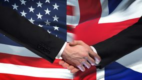 USA and Great Britain handshake, international friendship flag background. Stock footage stock footage