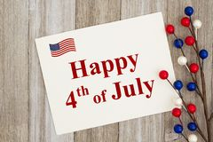 USA Happy 4th of July greeting card. Happy 4th of July text on a greeting card with a red, white and blue floral berry spray on weathered wood royalty free stock photography