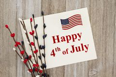 USA Happy 4th of July greeting card. Happy 4th of July text on a greeting card with a red, white and blue floral pip berry spray on weathered wood stock photo