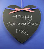 USA holiday Happy Columbus Day message sign greeting written on a heart shape blackboard. With red white and blue stars and stripes ribbon against a blue royalty free stock photo