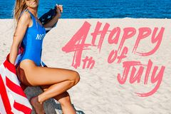 Beautiful cheerful woman holding an American flag on the beach stock image