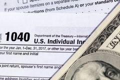 USA 1040 Individual Income Tax Return Form with one hundred dollar bills. Close-up royalty free stock images