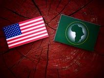 USA kennzeichnen mit Flagge der Afrikanischen Union auf einem Baumstumpf Lizenzfreie Stockfotografie