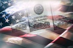 USA kennzeichnen und amerikanische Dollar Amerikanische Flagge, die im Wind und in 100 Dollar Banknoten im Hintergrund durchbrenn Stockbilder