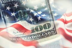 USA kennzeichnen und amerikanische Dollar Amerikanische Flagge, die im Wind und in 100 Dollar Banknoten im Hintergrund durchbrenn Stockfotos