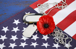 USA Memorial Day concept. USA Memorial Day concept with dog tags and red remembrance poppy on American stars and stripes flag on dark blue vintage wood table Royalty Free Stock Photos