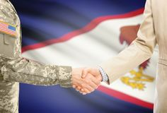 USA military man in uniform and civil man in suit shaking hands with adequate national flag on background - American Samoa. American soldier in uniform and civil Royalty Free Stock Images