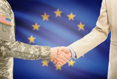 USA military man in uniform and civil man in suit shaking hands with adequate national flag on background - European Union. American soldier in uniform and civil Royalty Free Stock Images