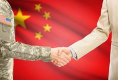 USA military man in uniform and civil man in suit shaking hands with adequate national flag on background - People`s Republic of. American soldier in uniform and Royalty Free Stock Images