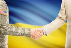 USA military man in uniform and civil man in suit shaking hands with adequate national flag on background - Ukraine. American soldier in uniform and civil men in Royalty Free Stock Photo