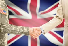 USA military man in uniform and civil man in suit shaking hands with adequate national flag on background - United Kingdom of Grea. American soldier in uniform Royalty Free Stock Photography