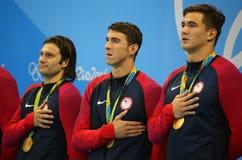 USA mäns laget för relän för den 4x100m medleyn Cory Miller (v), Michael Phelps och Nathan Adrian firar seger Arkivbild