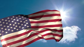 USA national flag blowing in the breeze. On blue sky background with sun and clouds stock video