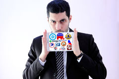 USA election parliamentary political party logos and icons. Arab businessman holding white tablet and emblem of top election parliamentary political parties for Royalty Free Stock Photo