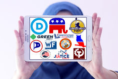 USA election parliamentary political party logos and icons. Arab muslim woman holding white tablet and emblem of top election parliamentary political parties for Stock Photography