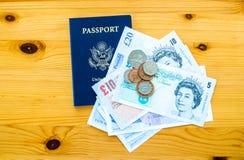 USA-pass och brittpengar på en tabell Royaltyfri Fotografi